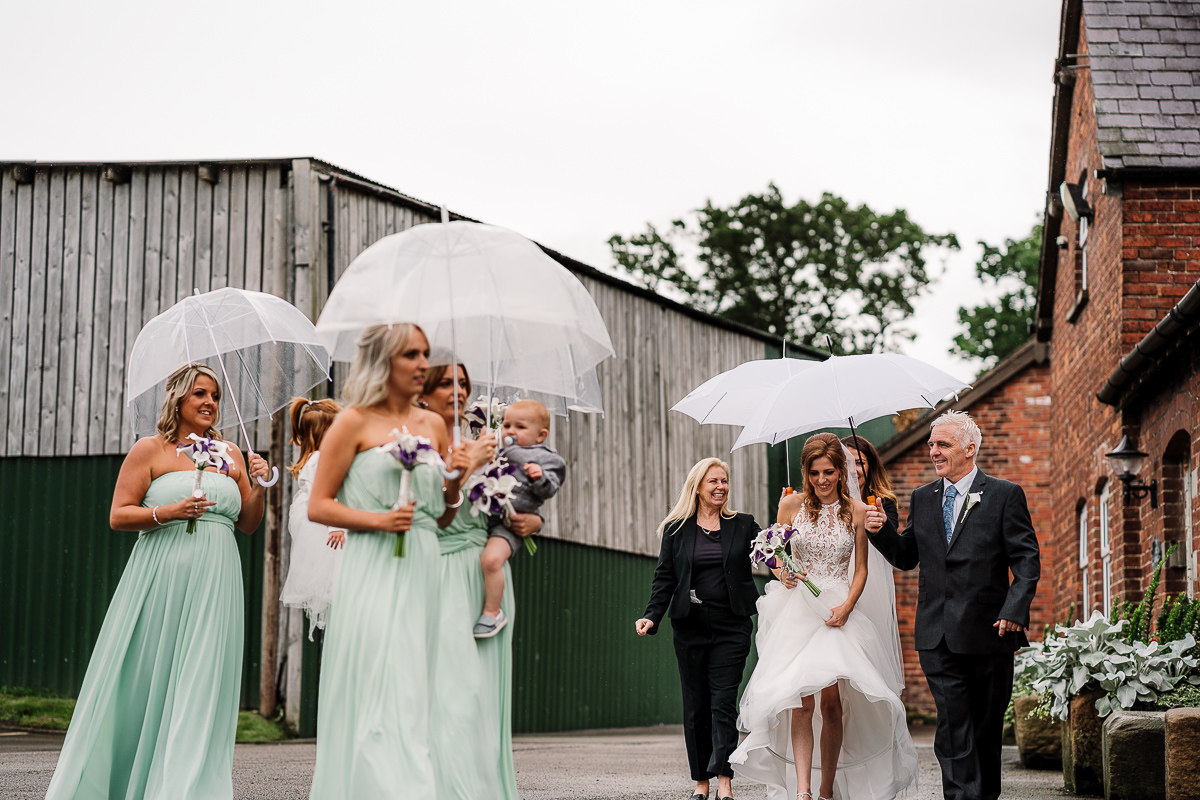 Bride and bridesmaids walking with umbrellas