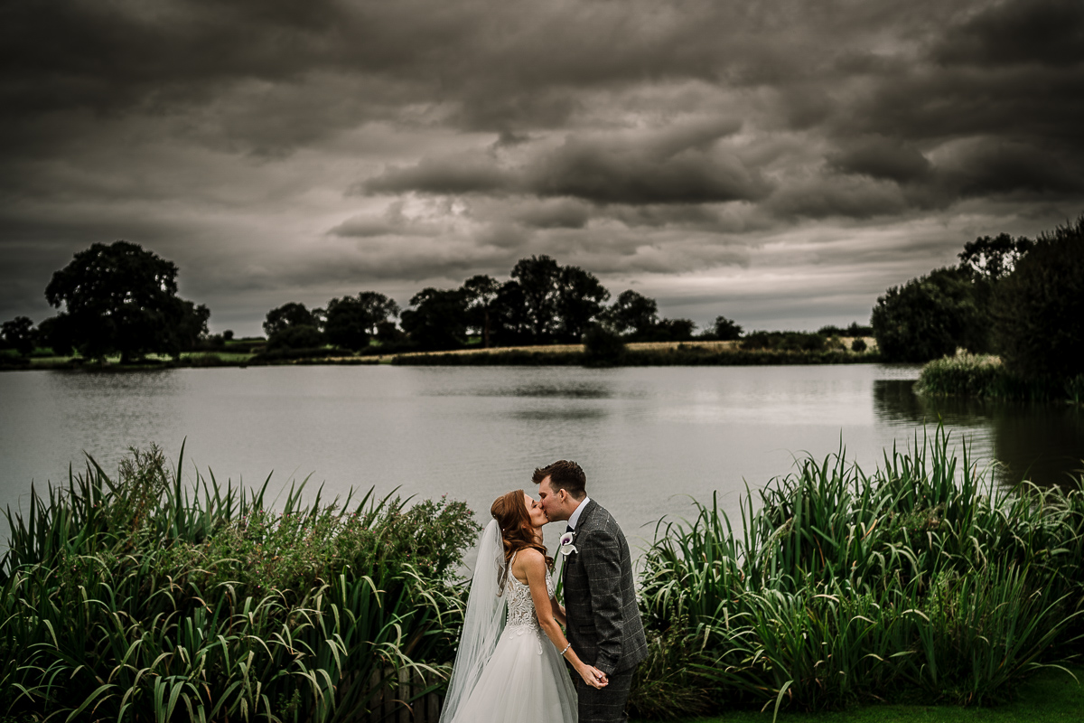 Bride and groom kissing by the lake