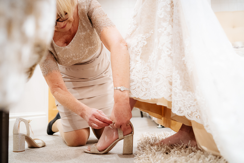 Mother of the bride fastening the bride's shoe