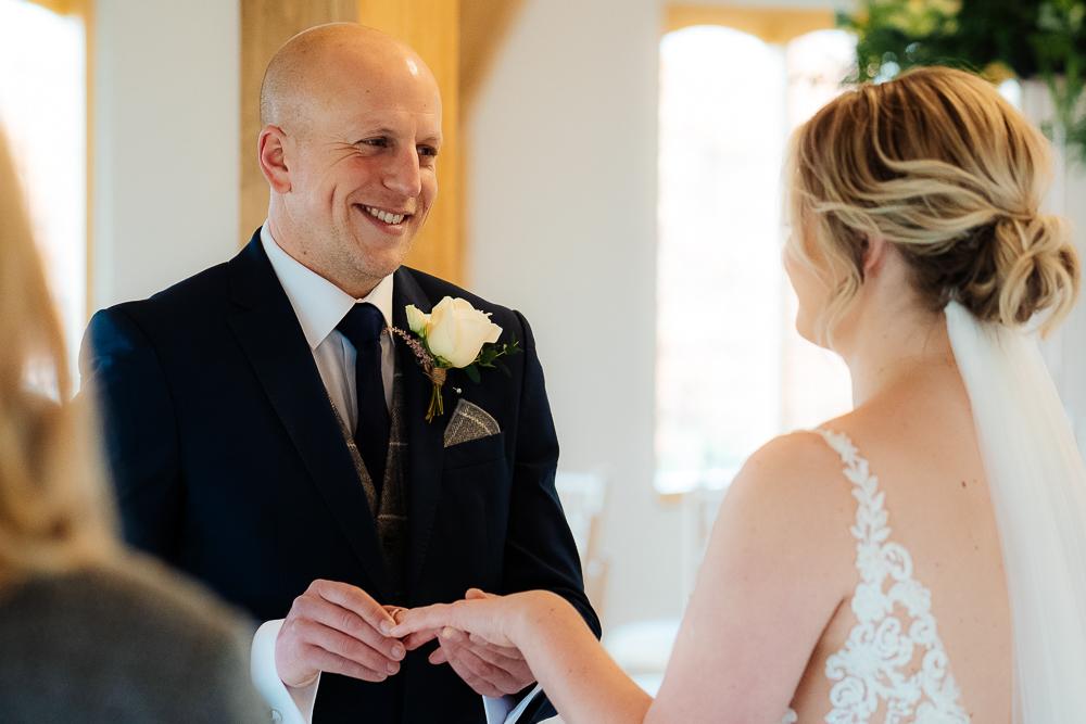 Groom putting ring on bride's finger