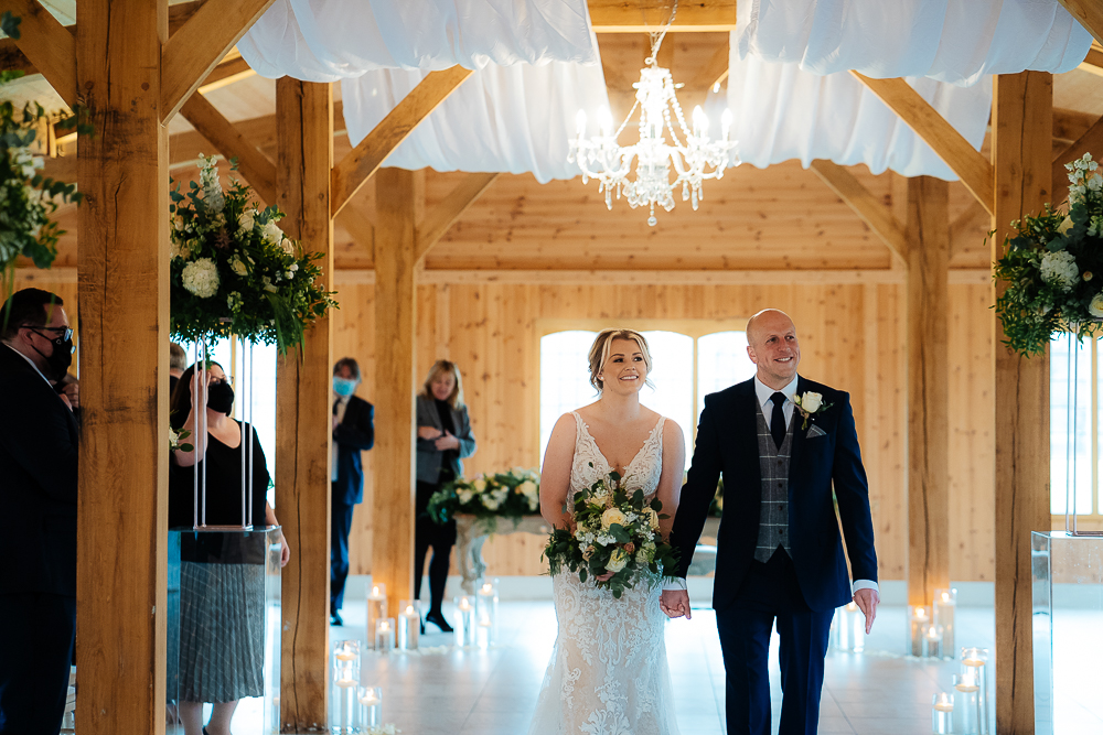 Bride and groom walking back up the aisle at Merrydale Manor