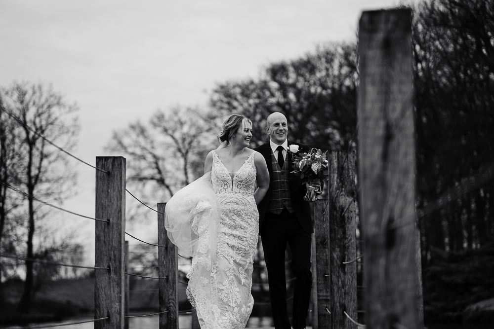 Bride and groom walking on jetty at Merrydale Manor