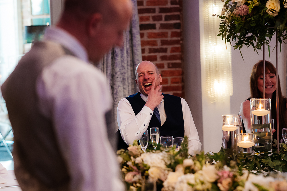 Brother of the groom laughing at the speeches