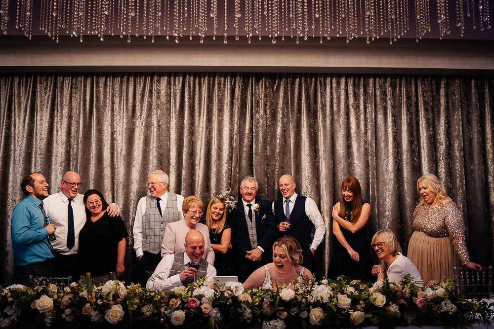 guests laughing at video messages with the bride and groom