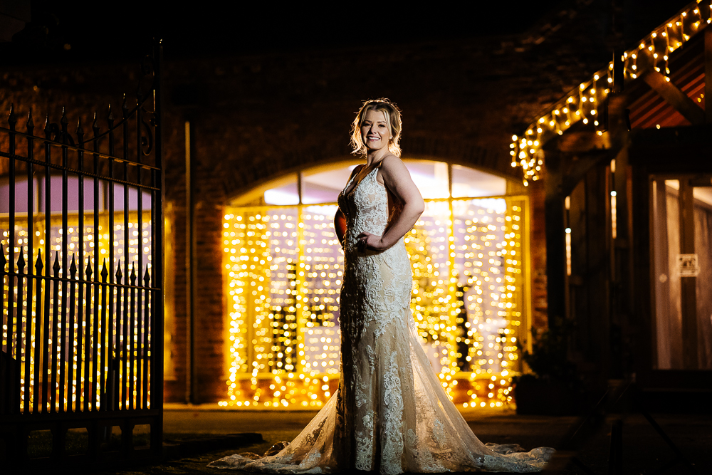 full length photo of bride in front of fairy lights