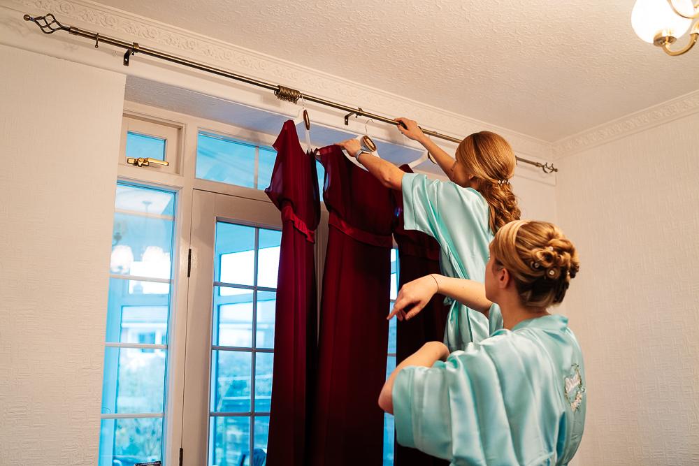 bridesmaids hanging dresses up