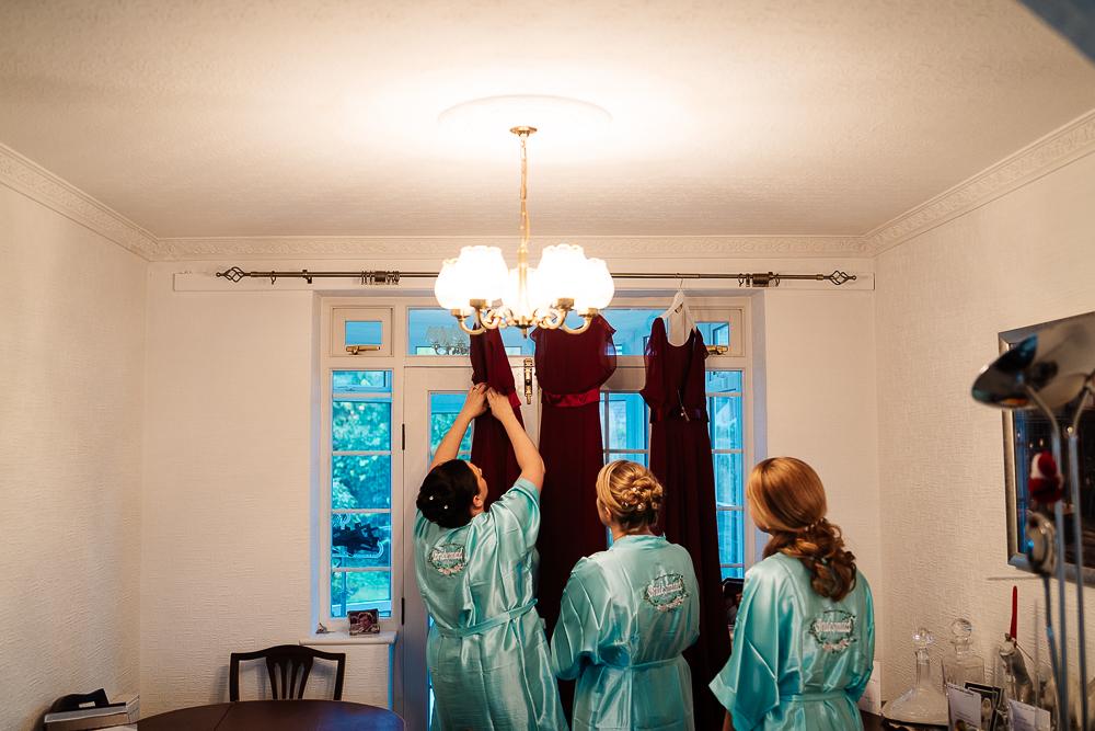 bridesmaids adjusting dresses on hangers