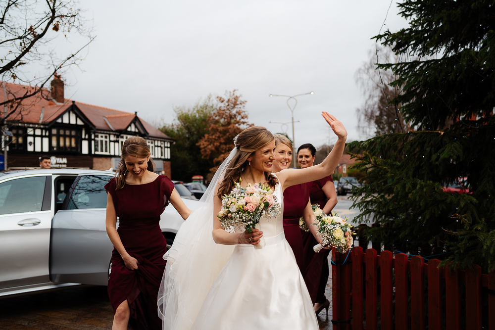 bride waving at people outside church