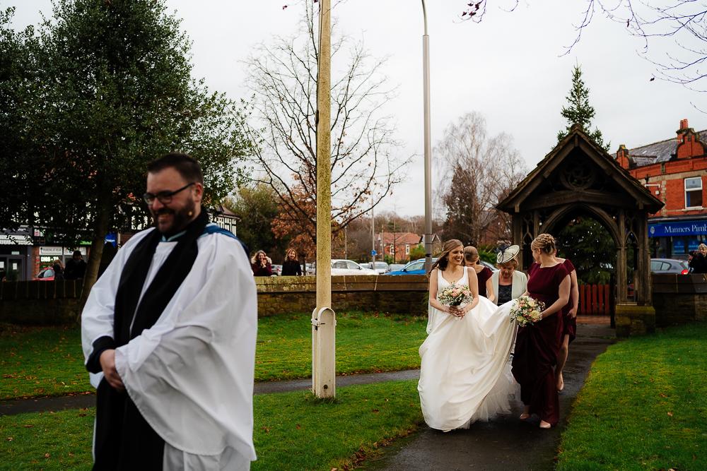 vicar, bride and bridesmaids walking down church path