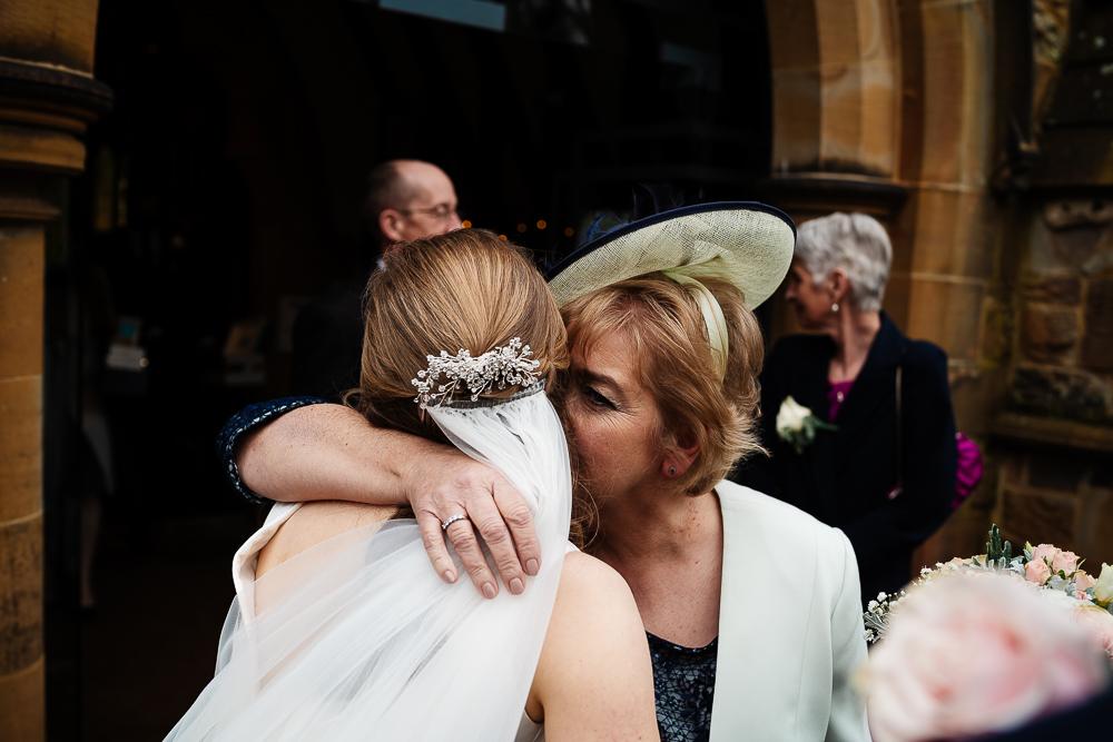 mother of the bride hugging bride