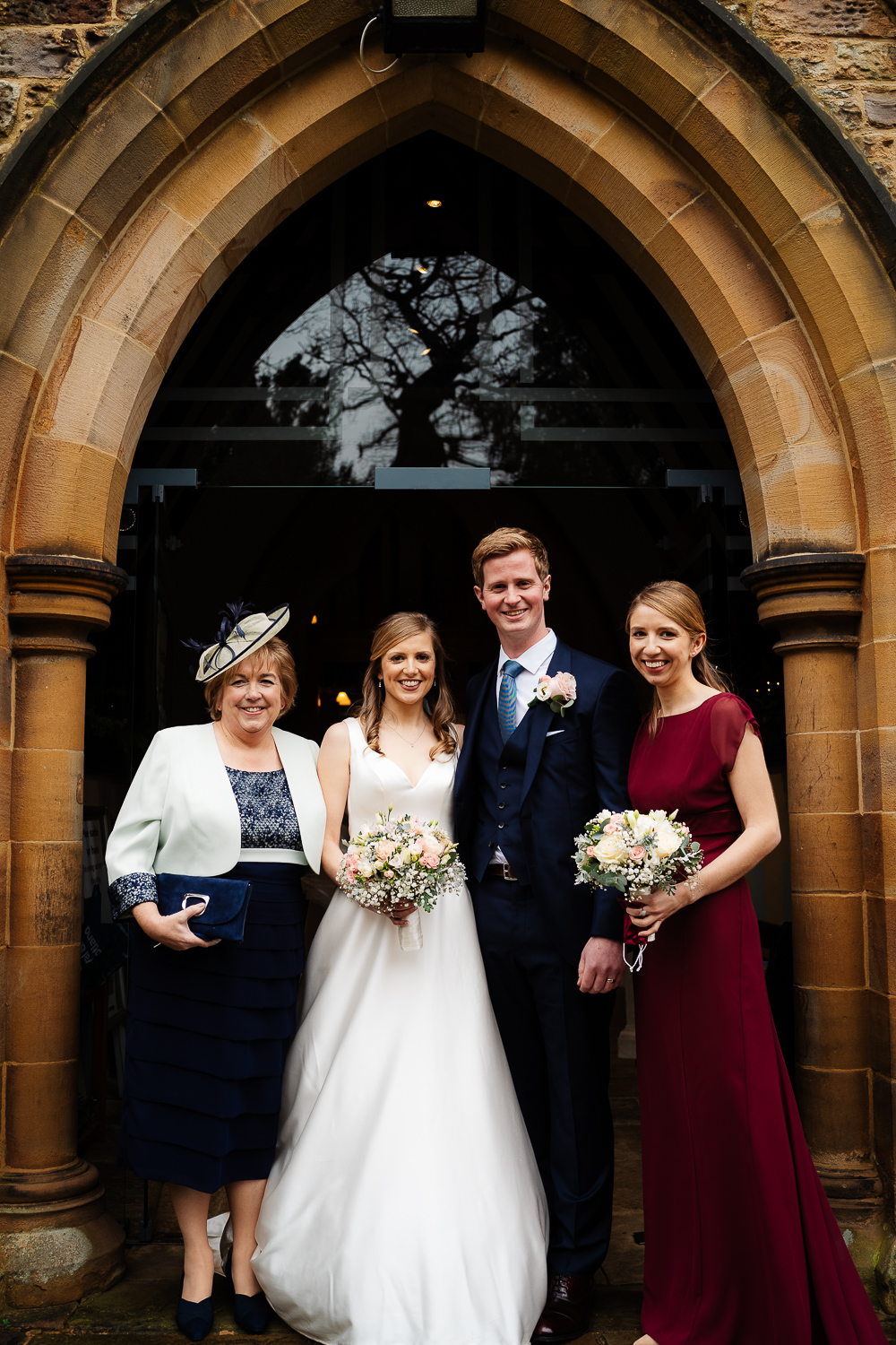 bride and groom with mother of the bride and bridesmaid