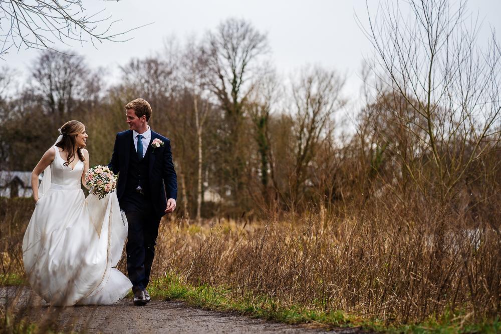 bride and groom walking by poynton pool